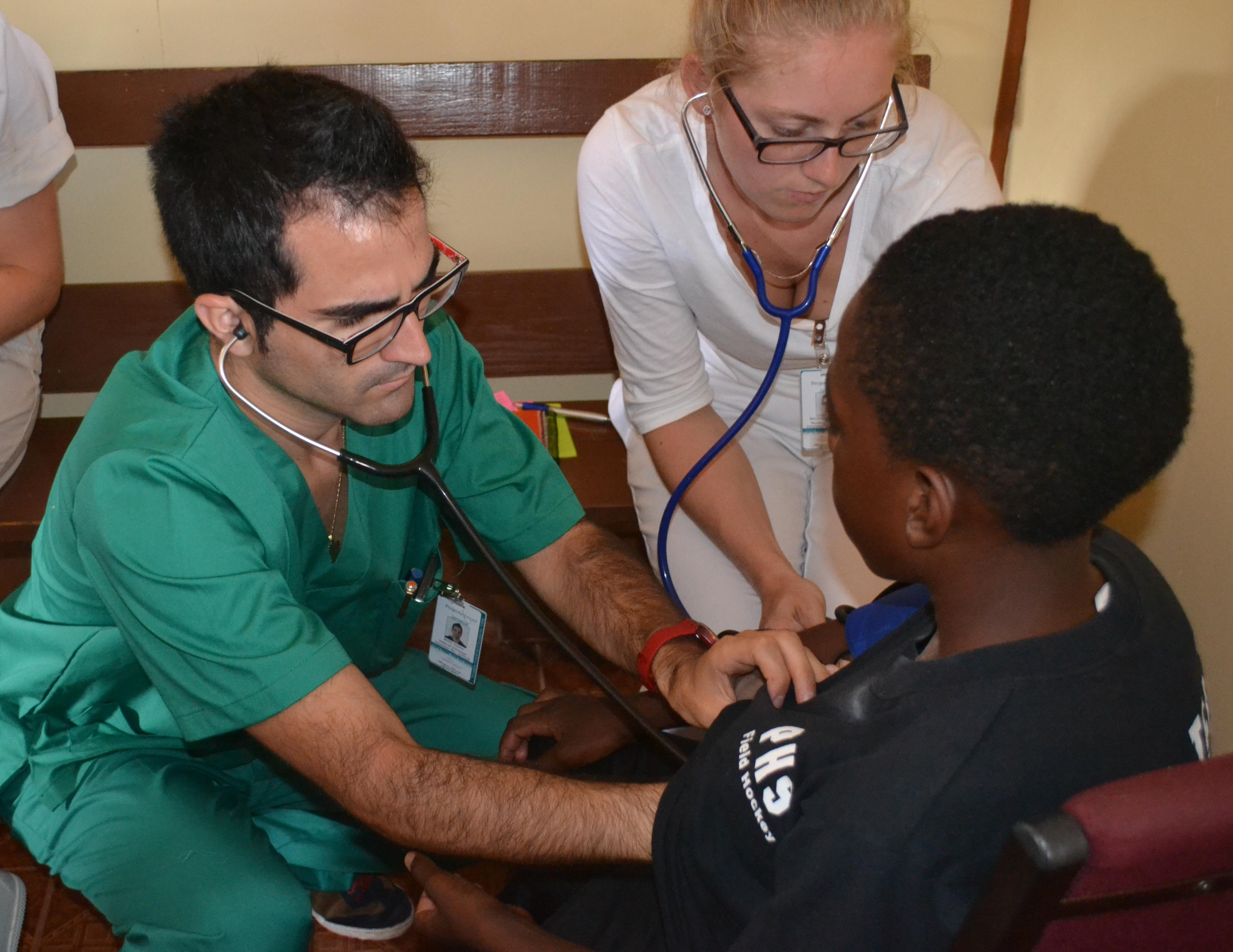 Male and female interns examine a young boy's chest at a Community Outreach Day in Jamaica.